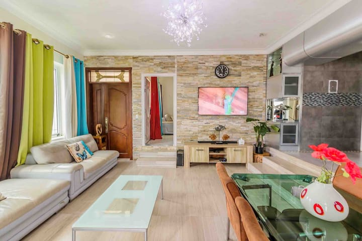 """Section of living room with 65"""" smart tv with Netflix, YouTube etc and Bluetooth sound bar"""