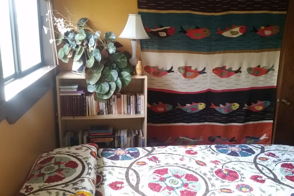 Plenty of books (classics and modern) and a fish tapestry to top it off
