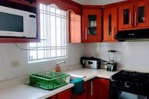 cocina completamente equipada  con estufa con horno, refrigerador y   utensilios para cocinar