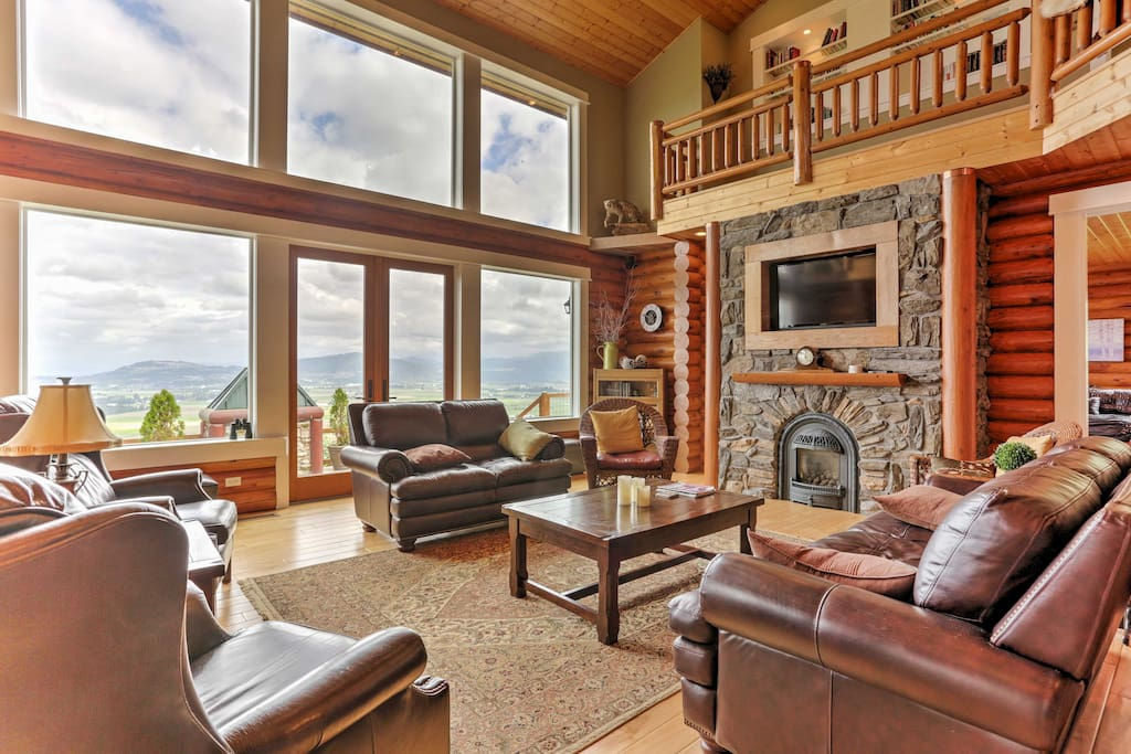 Relax in the family room that boasts floor-to-ceiling windows, cathedral ceilings, a stone, gas fireplace, plush leather furniture, and a flat-screen cable TV.