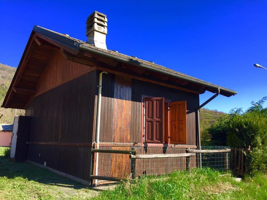 Chalet visto da fuori, completamente in legno, con un piccolo recinto e una siepe che vi farà godere di tutta la privacy di cui avete bisogno!