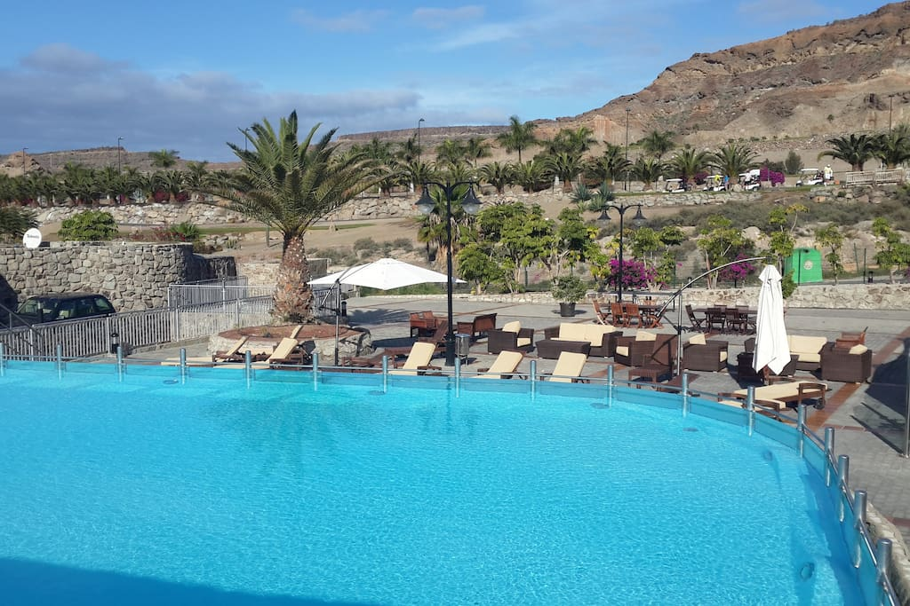 Glass sided heated communal pool with plenty of loungers and seating.  Right beside supermarket and restaurant. 2 minutes from villa.