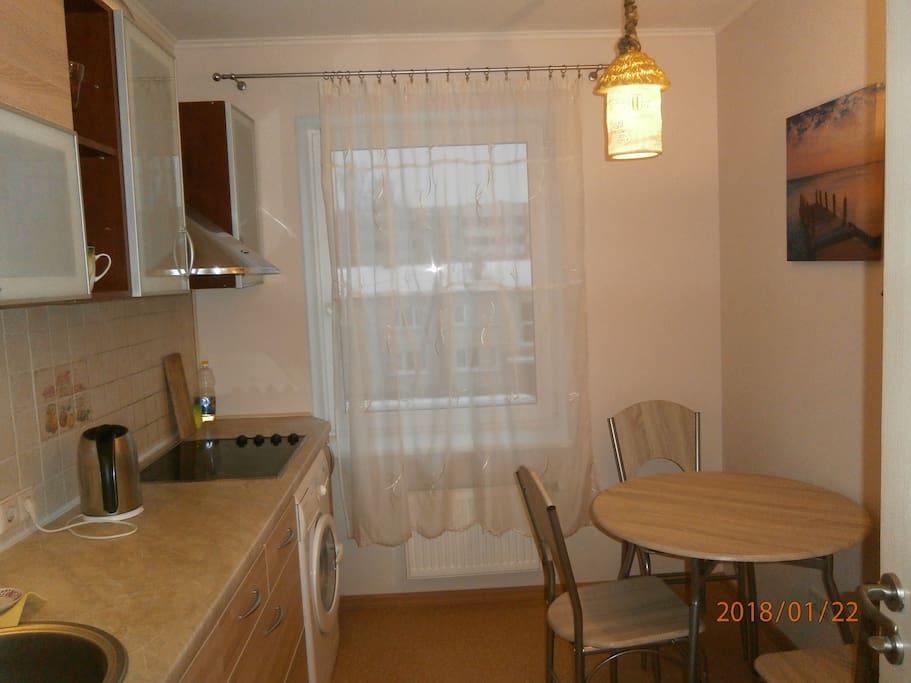 kitchen with washing machine, glass table and big fridge