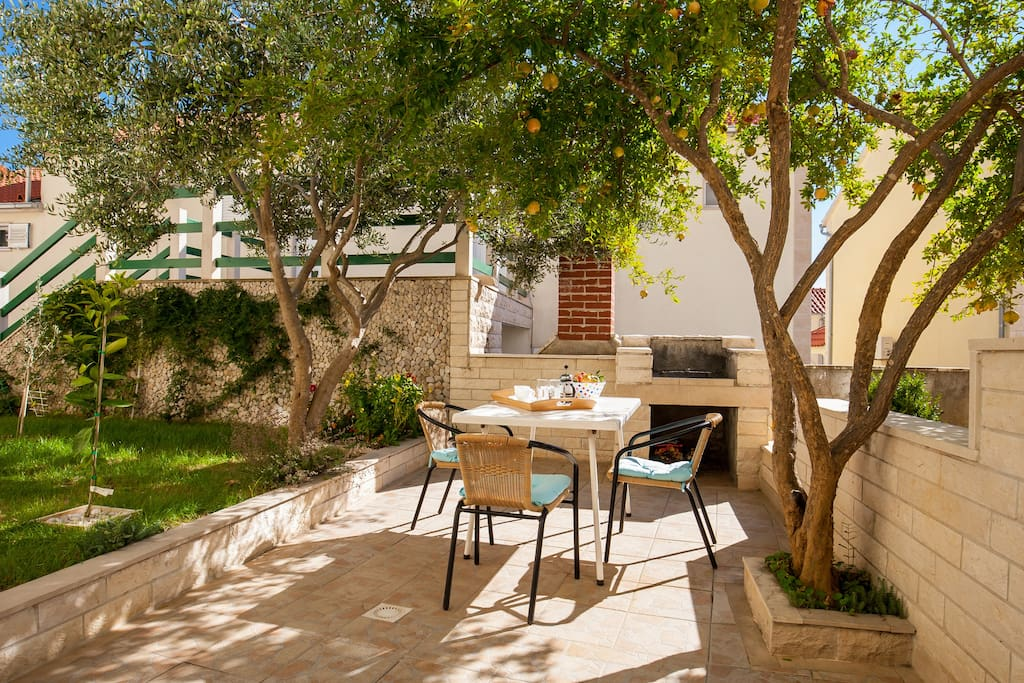 lovely terrace in greenery with dining table and BBQ