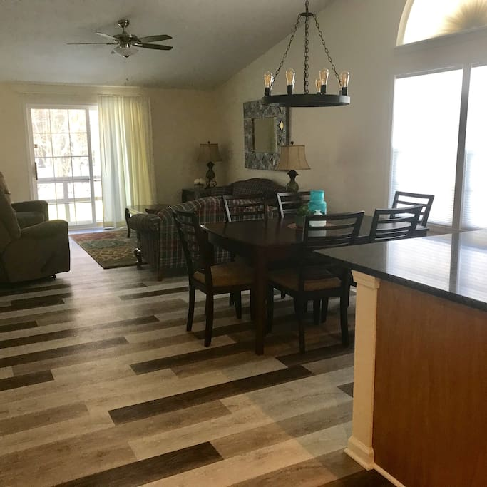Open floor plan. View from kitchen through DR into living area. Sliding glass doors open onto back deck with view of woods.