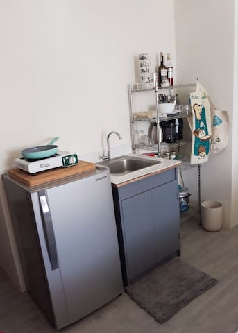Kitchenette  Refrigirator / Buthane Gas Cooker / Induction Cooker / Electric kettle / French coffee press / Moka Express / Rice cooker   Plates/ bowls/ mugs /glasses / utensils/ grocery bags/ pots / pans/ towels
