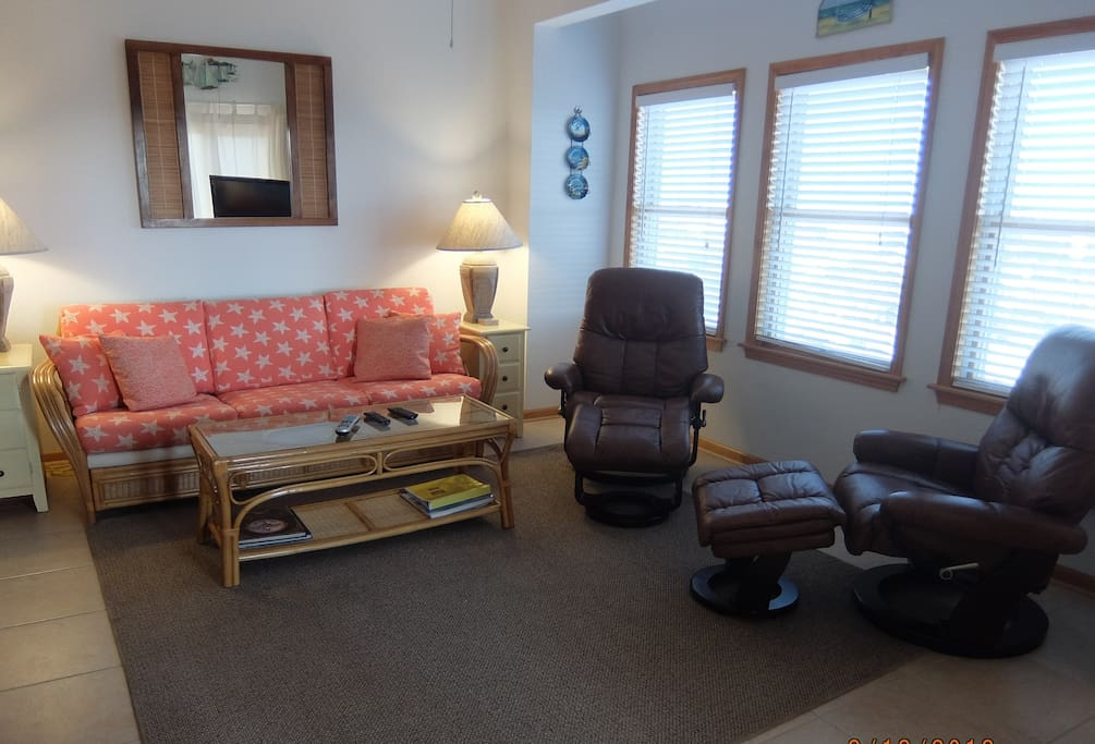 Newly upholstered sofa bed + 2 new leather, swivel recliners with footrests for your comfort.