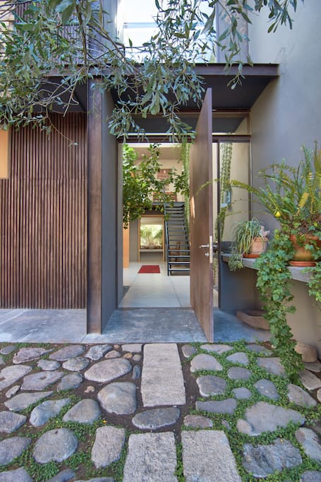 Pivoting metal door opens from carport to entry. Come on in!