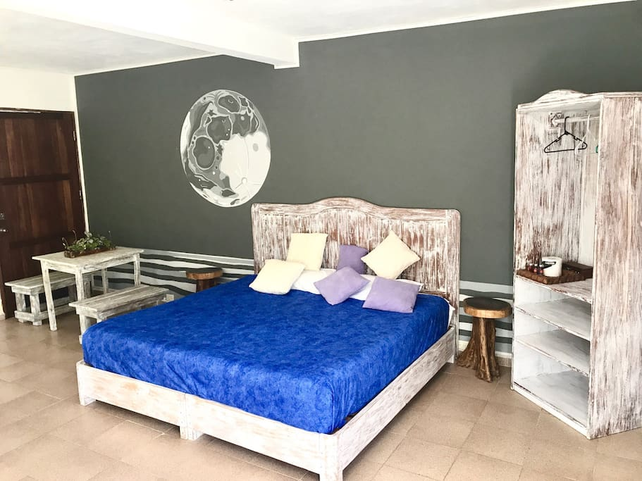 King bed, closet and small laptop friendly table beneath a moon mural