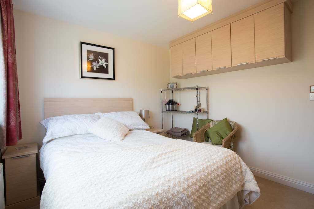 Double bed with fitted cupboards & wicker chair