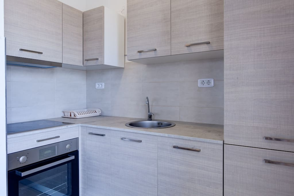Apartment has a dining table and 4 chairs. The kitchen is fully equipped so it includes a cooker, a cooker hood, fridge with freezer, dishwasher.