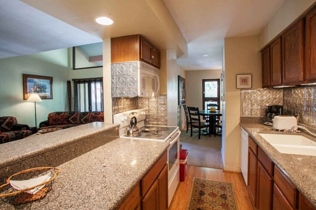 Open fully equipped kitchen with bar seating for 2, opens to dining table and living room.