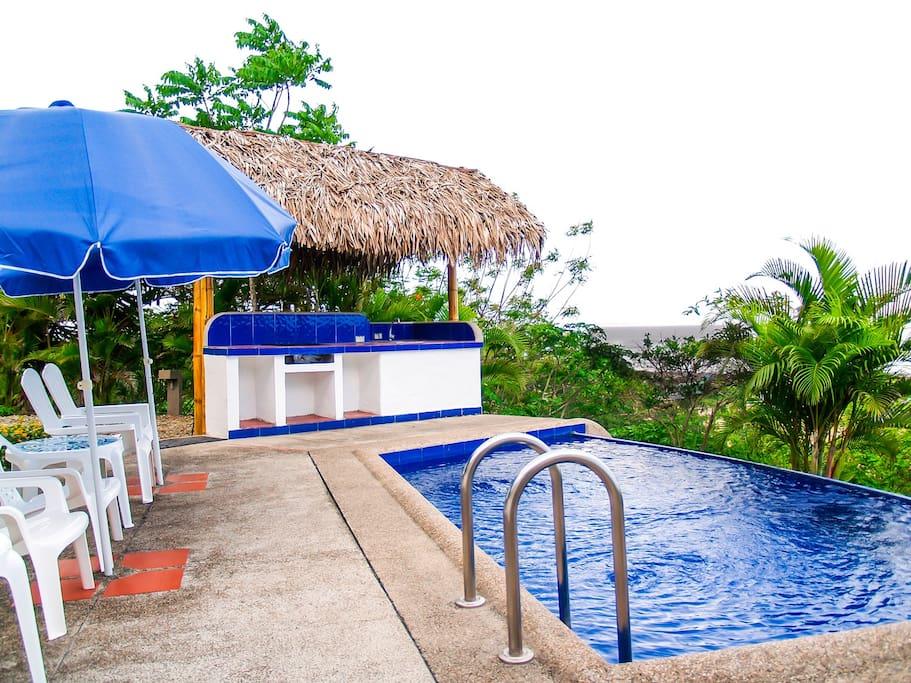 piscina tipo infinity edge con vista al mar, zona para tomar sol con sillas y parasoles y BBQ
