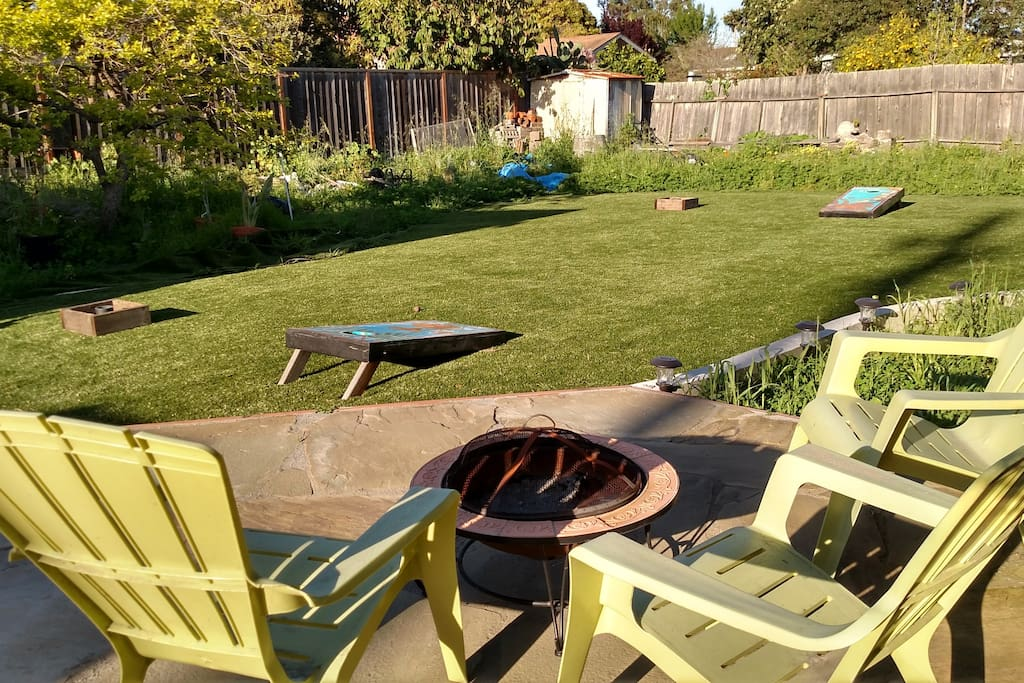 Huge backyard with deck, bbq, firepit, cornhole, washers, and ping pong