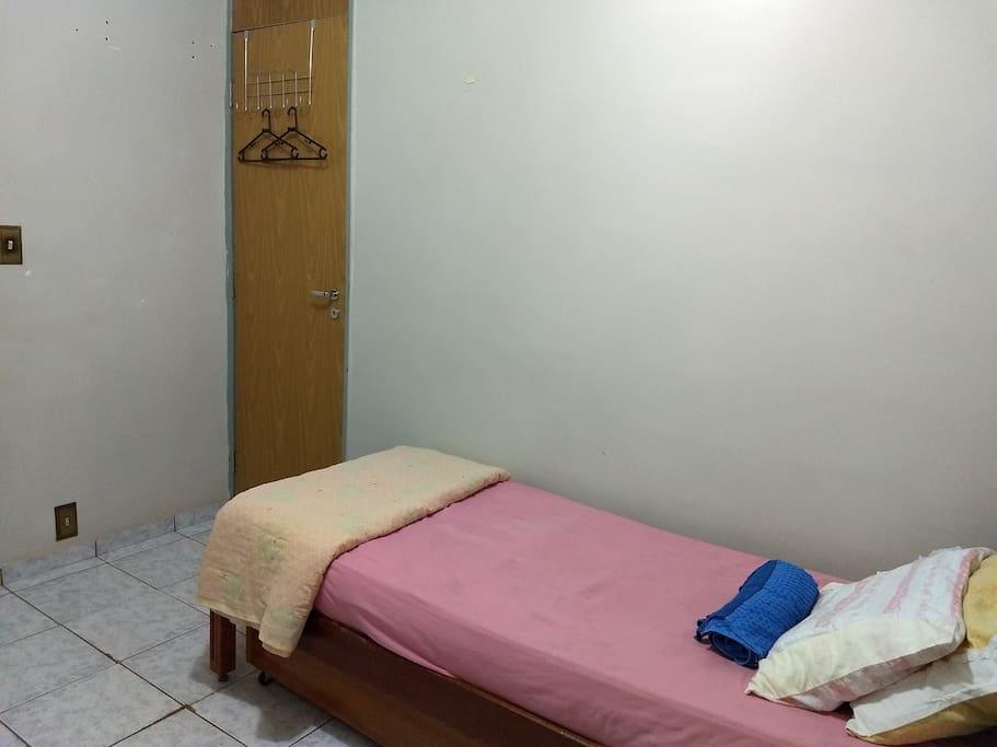 Cabideiro para roupas, tomada aos pés da cama, travesseiros, cobertor e toalha, porta com tranca