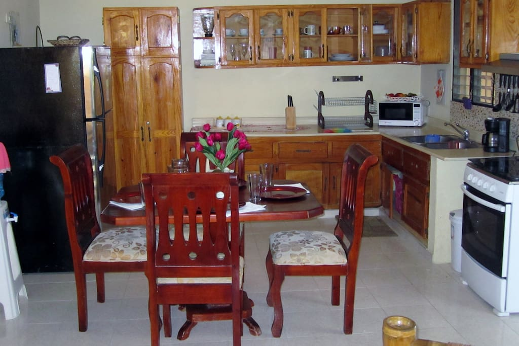 The eat-in kitchen with full gas stove, microwave, toaster oven, water cooler and four person dining table.