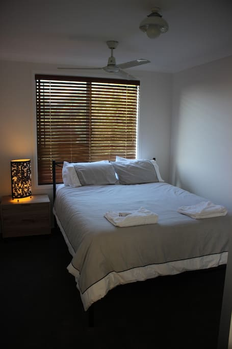 Bedroom complete with comfortable QS bed & quality linen, side table and lamp