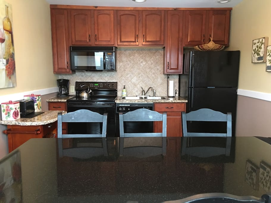 Fully equipped kitchen has granite countertops  with a view of mountains & ski jump.