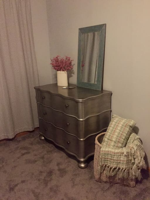 Dresser for guests, mirror, and extra blankets in the bedroom