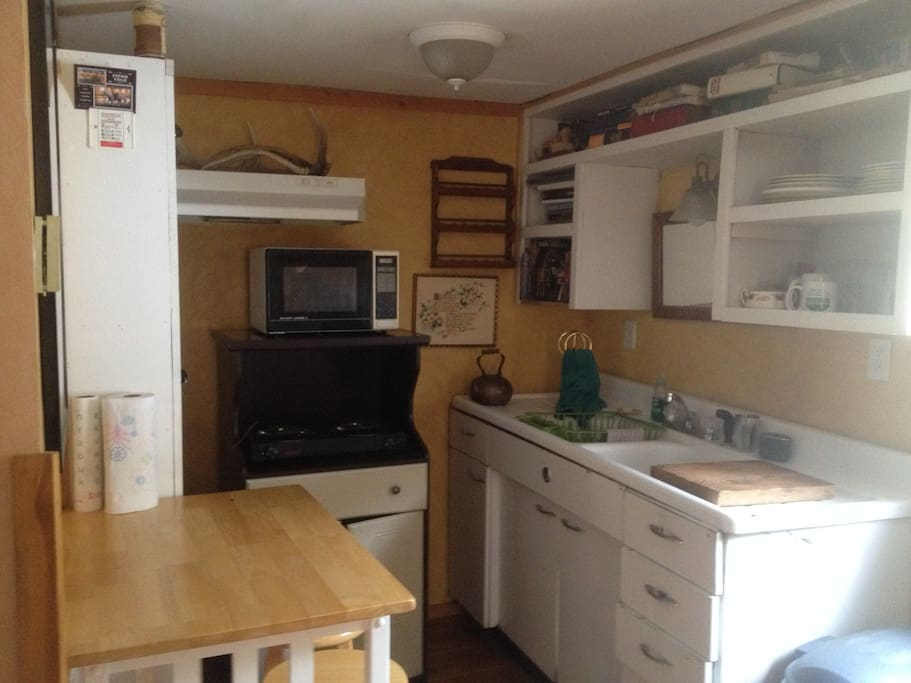 Kitchen with sink, microwave, small table for 2, and hot plate for cooking.  Kitchen has dishes, silverware and a few pots and pans.