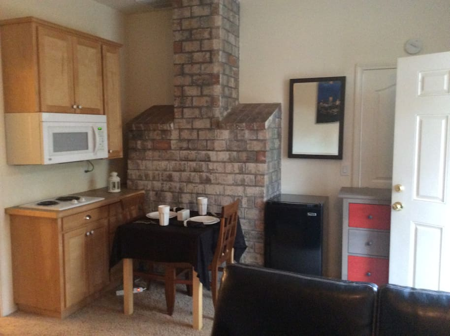 Dining area with Microwave, Refrigerator, table & 2 chairs.