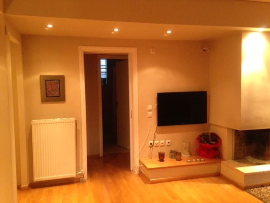 Living room with wall mounted Smart TV, internet, high-speed Wi-Fi and indoor fire place.