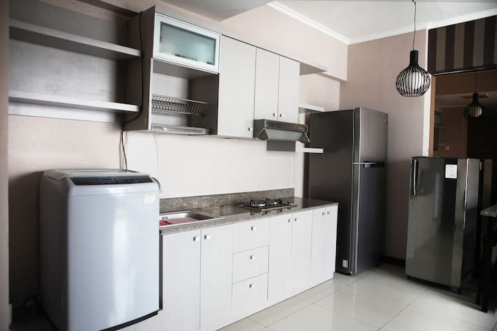 Kitchen area with fridge, gas stove, and washing machine