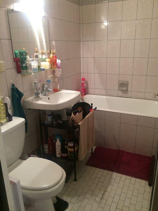 Salle de bains avec baignoire et meuble