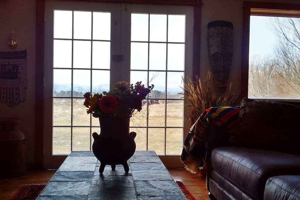 Antique French doors open to the organic meadows and Adirondack mountain views.