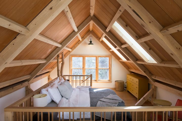 The full height sleeping loft, with night sky views and luxury linens.   See the stars from bed!