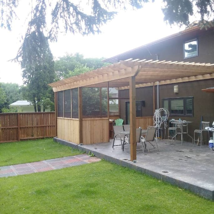 Nicely landscaped backyard, featuring large covered patio, outdoor kitchen, screened in hot tub area.