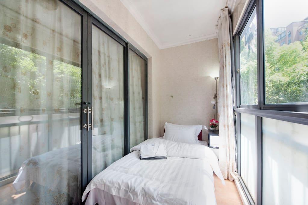 这是一个与客厅连接的封闭阳台改成的小房间,1米宽的单人床,有空调。