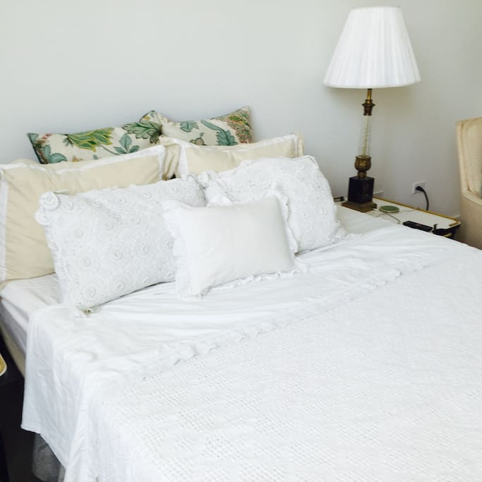 beautiful comfortable memory foam bed with cotton linens and down pillows.