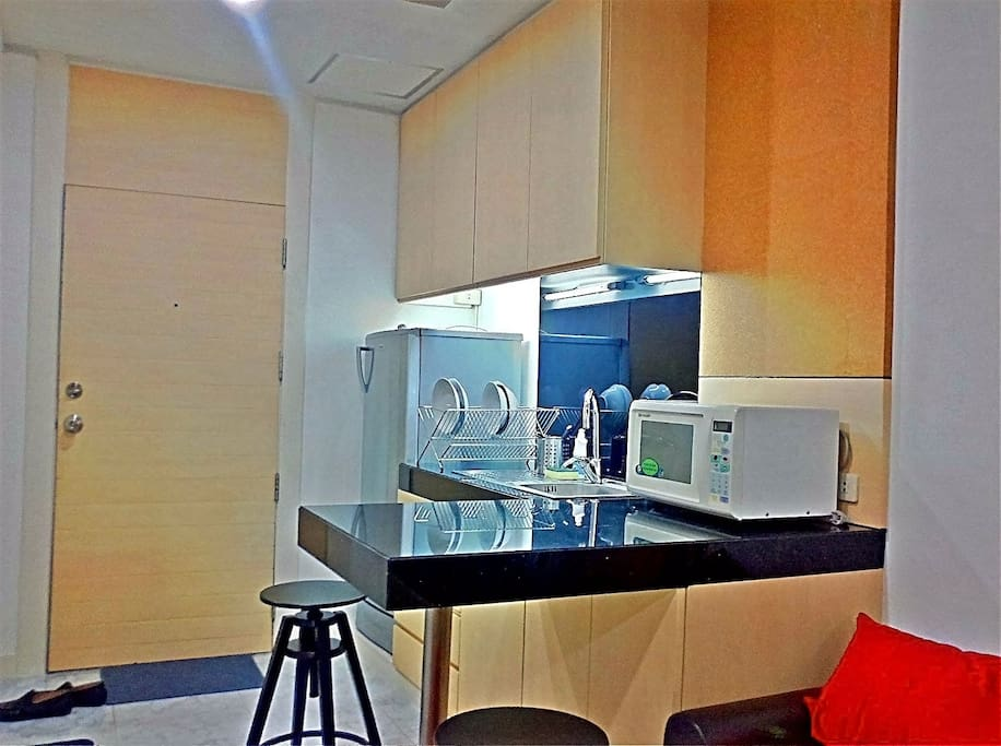 Mini kitchen with utensils, plates, glasses, microwave and refrigerator. Good for heating up take away food.