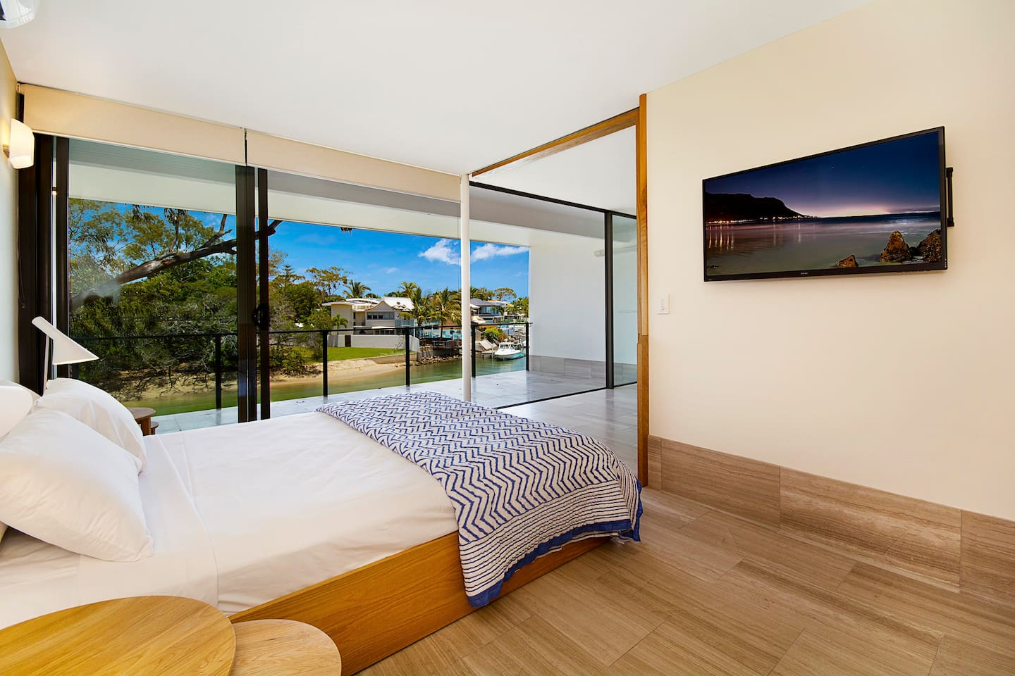 Master bedroom with sliding cavity door revealing Noosa River with sunset views