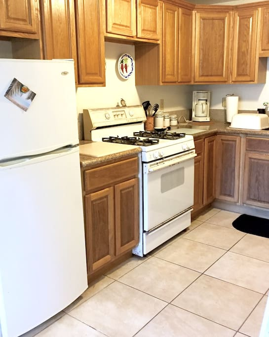 Full sized kitchen with gas stove, refrigerator, microwave, toaster oven and other amenities.