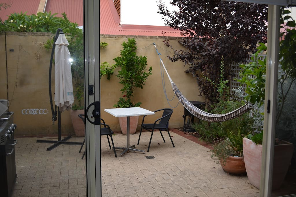 The lounge spills onto a sunny courtyard with BBQ, outdoor setting and hammock