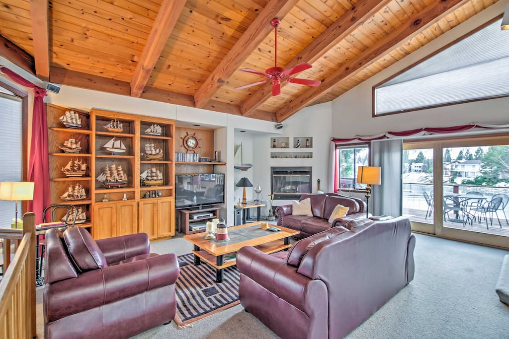 The living room boasts tall, vaulted ceilings and window-framed outdoor views.
