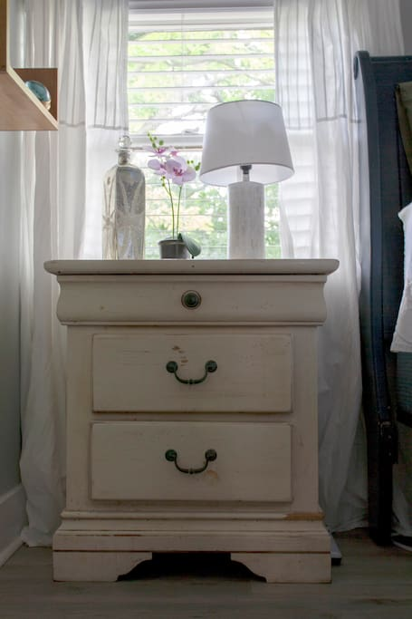 A nice nightstand and reading light is available for you as you snuggle in bed.