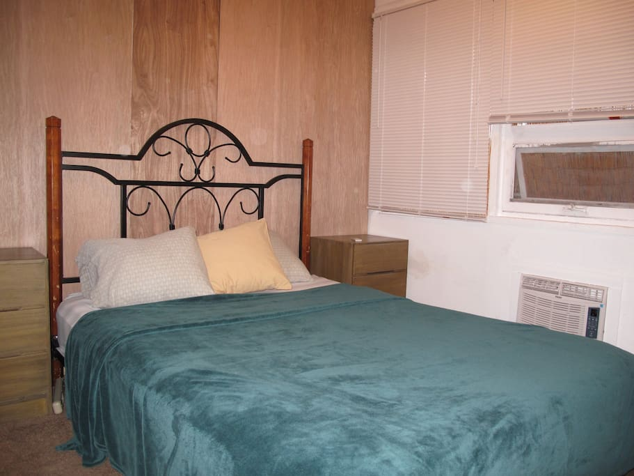 very small bedroom with a loud a/c, small window, and a ceiling fan