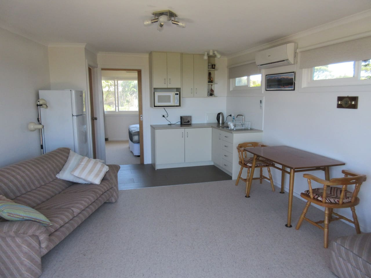 Spacious, bright living room with kitchenette, opening onto balcony with ocean view. Separate bedroom and private bathroom.