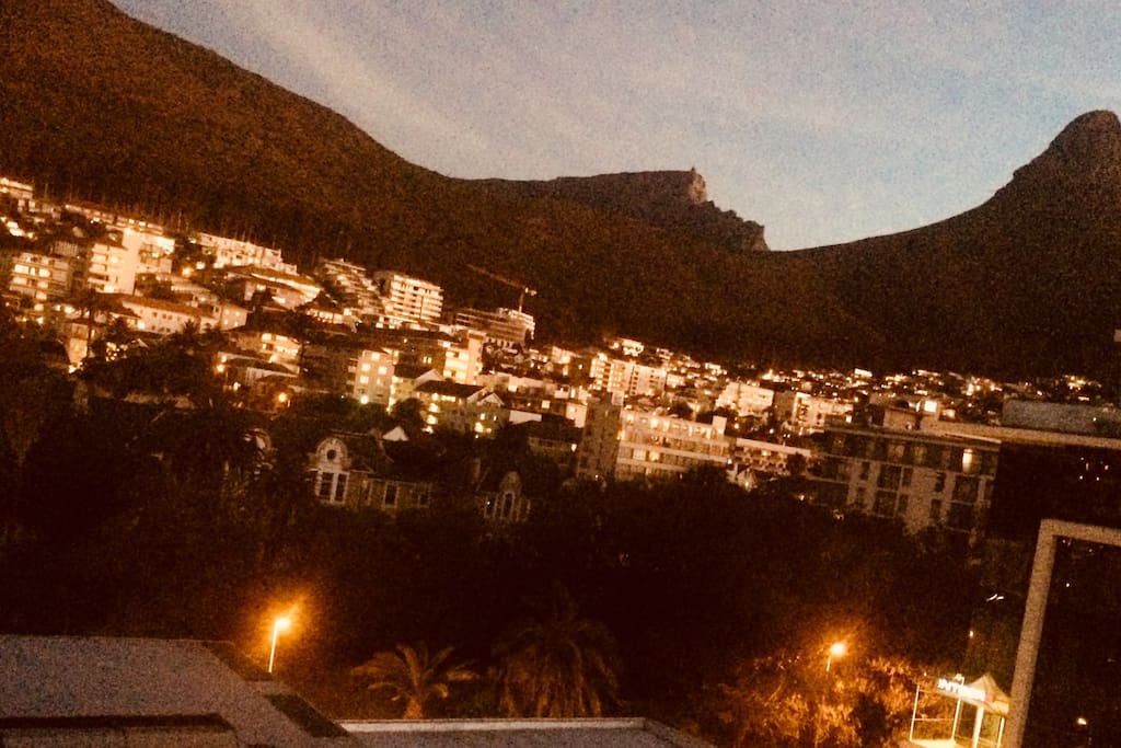 Sunset gives a special light to the homes under Signal Hill , Lion Head & Table Mountain