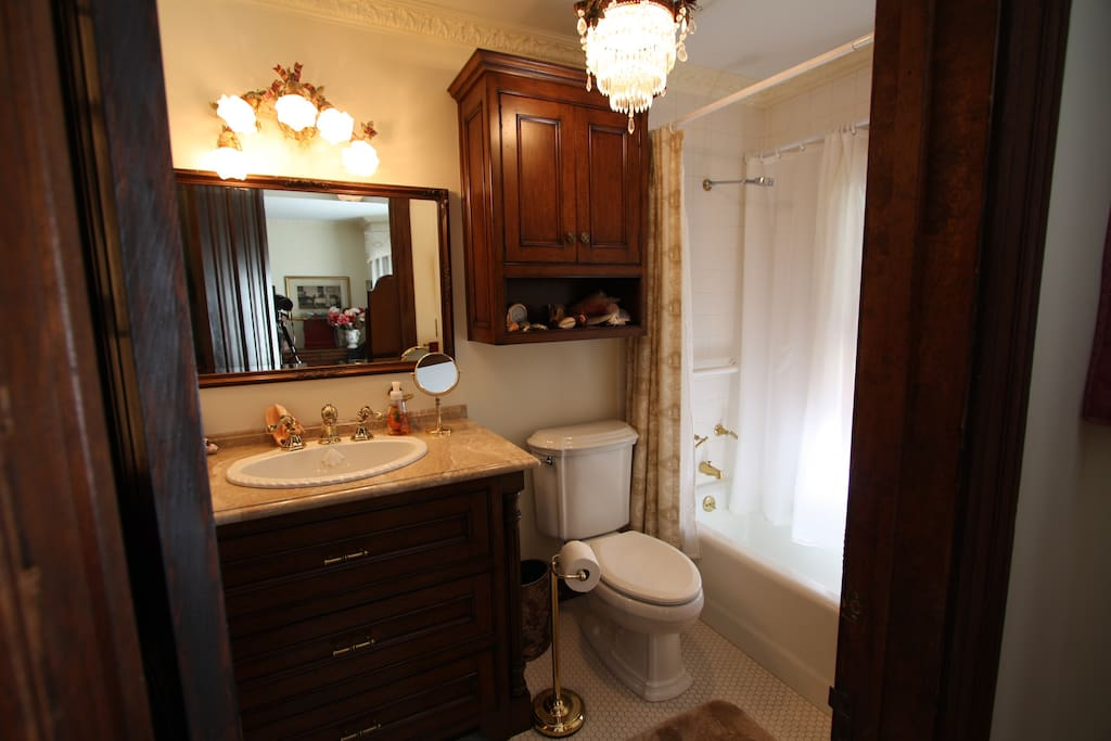 Complete full bath with shower, tub and granite counter top sink.
