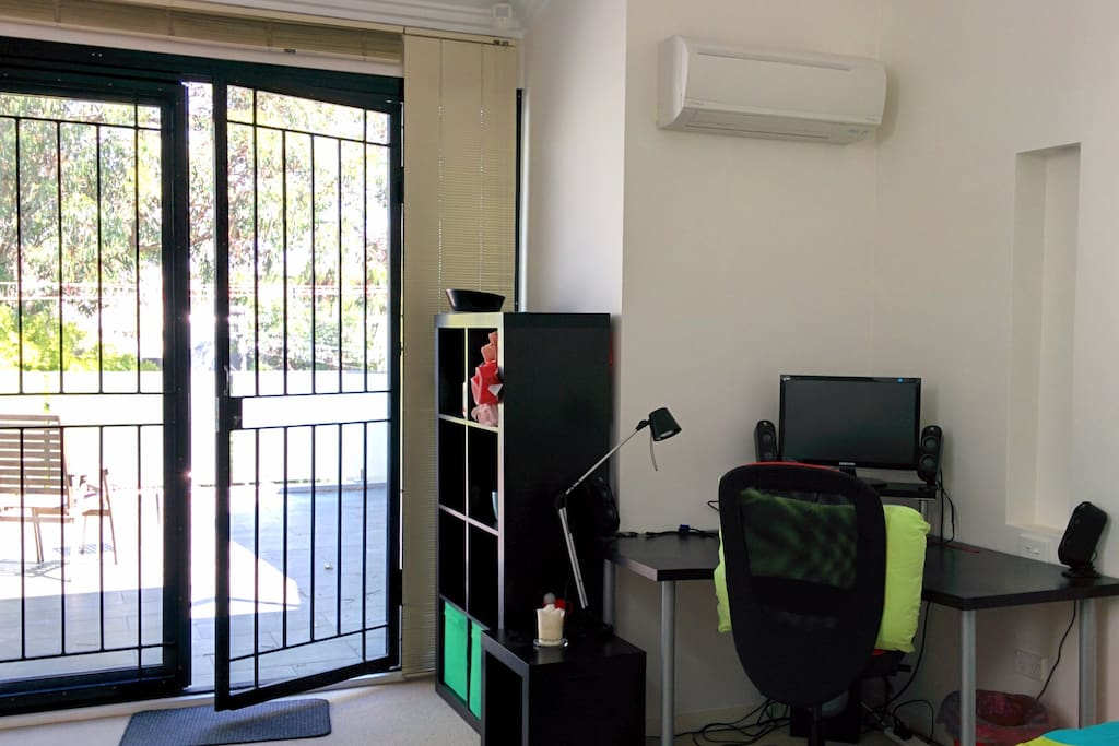 Desk, air conditioning, storage and full fly screen & glass doors to sunny balcony