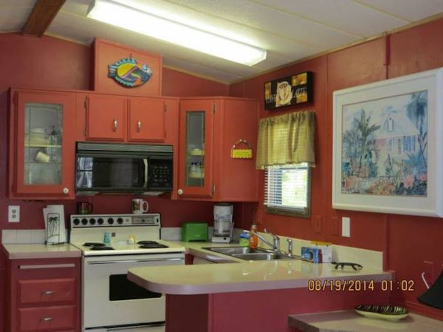 full kitchen with dishes, pots, pans, blender, full refrigerator, stove and utensils!