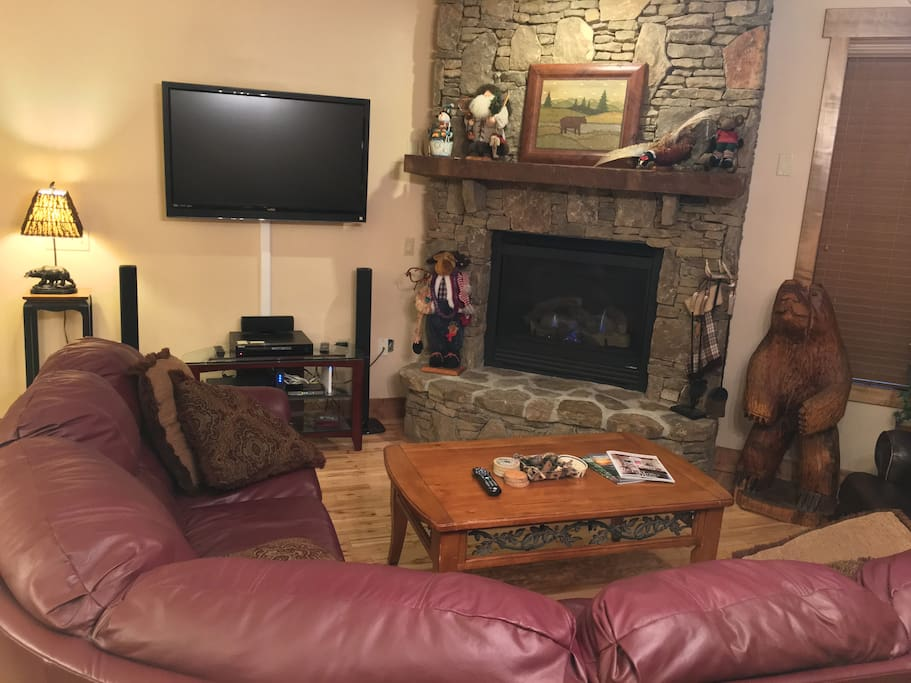 Living room. Large sectional couch, recliner, flat screen TV, and gas fireplace