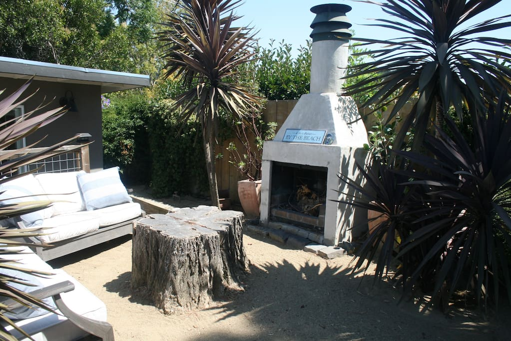 """Outside """"beach"""" area with wood-burning fireplace and two comfortable couches"""