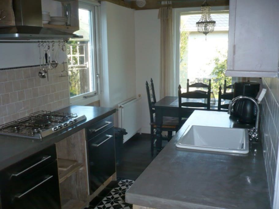 De keuken met een 6 pits gasfornuis en een afwasmachine