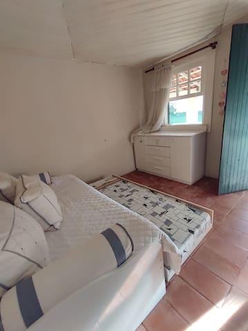 Quarto com cama e bicama, com porta para acesso ao quintal