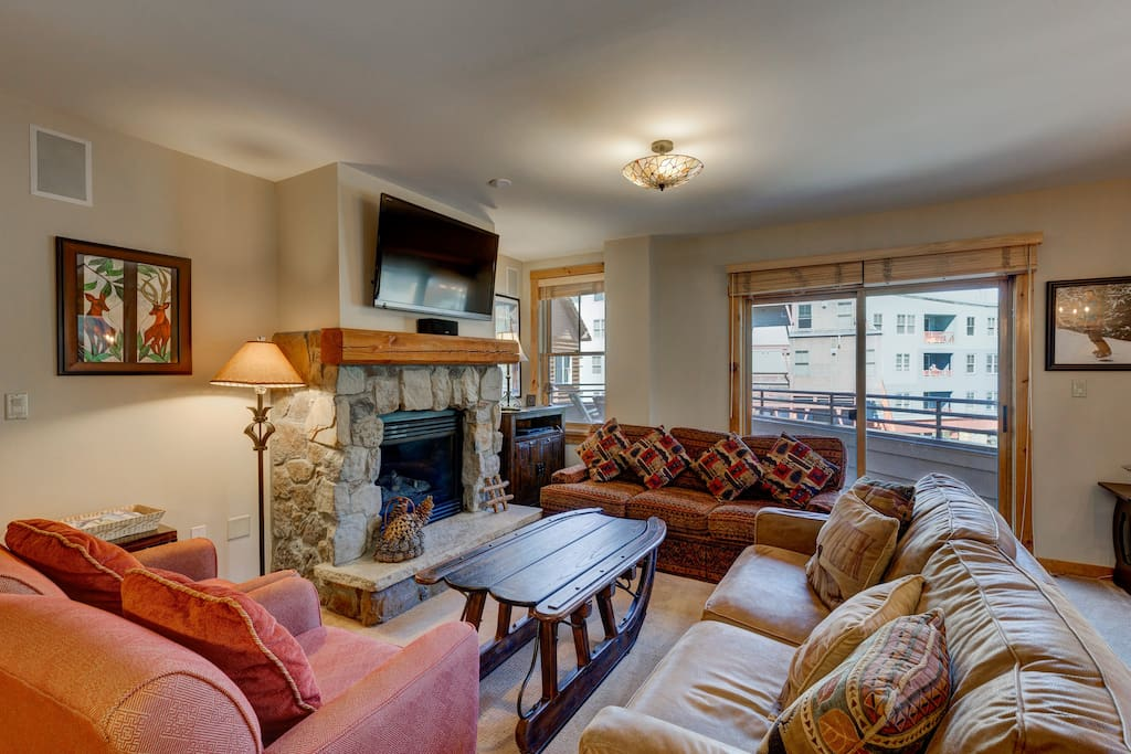 The living area features a flat screen TV mounted above a beautiful gas fireplace and a queen-sized sleeper sofa.